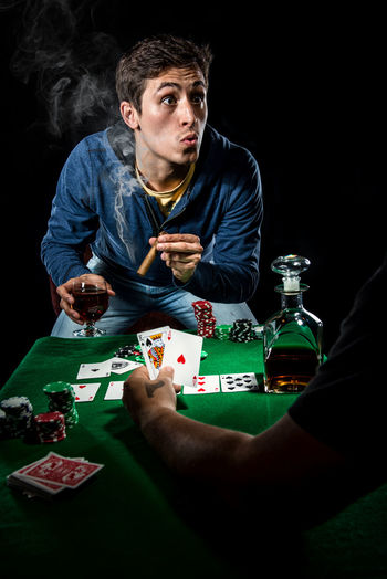Poker player. Gambling concept Blackjack Casino Gambling Jackpot Man Poker Smoking Addiction Alcohol Cards Cigar Entertainment Gambler Gambling Gambling Chip Game Male Player Playing Card Games Poker - Card Game Poker Chips Poker Game Smoker Studio Shot Young Adult