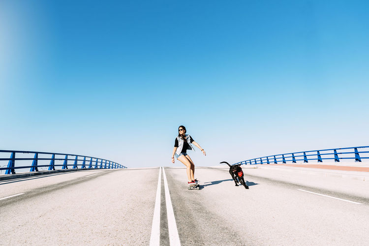 Dog running with woman skateboarding against blue sky