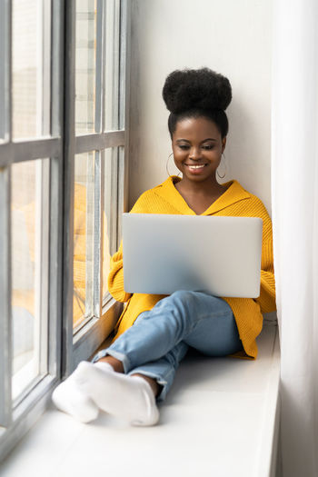 Smiling woman sitting at home while looking at laptop