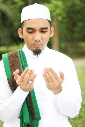 Man In Traditional Clothing Praying Against Trees