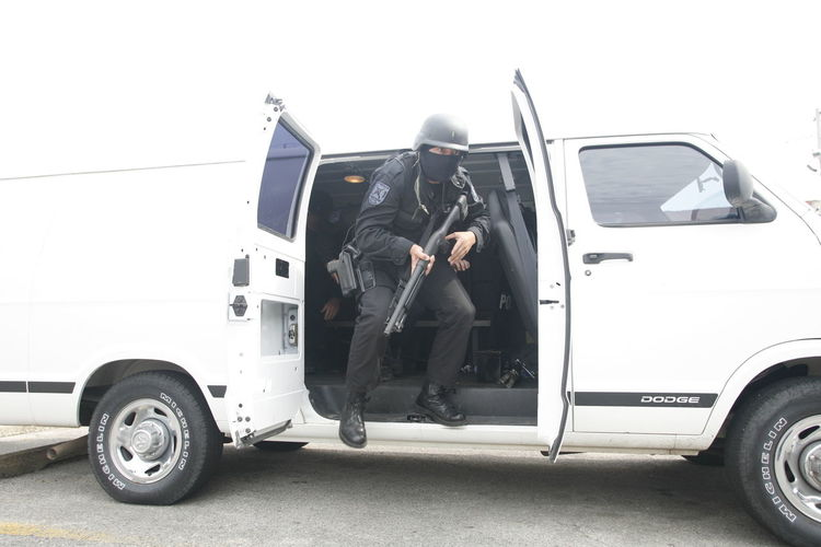 SWAT team member leaves van. Ar15 Clear Sky Day Full Length Land Vehicle Law Enforcement Leisure Activity Low Section Mammal Men Mode Of Transport Outdoors People Police Real People Sky Stationary Swat Togetherness Transportation Two People
