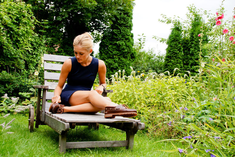 Young woman sitting on chair at yard