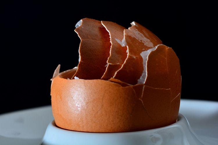 Close-up of broken egg against black background