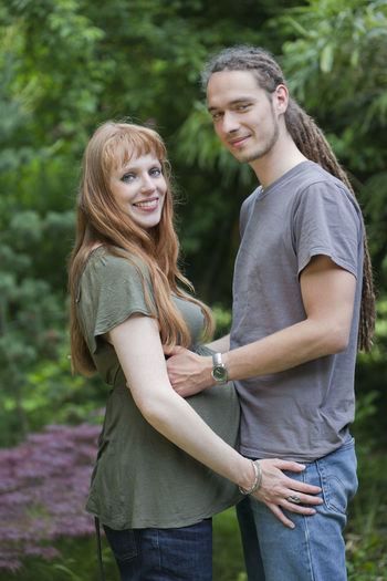 Portrait of man standing with pregnant woman against trees