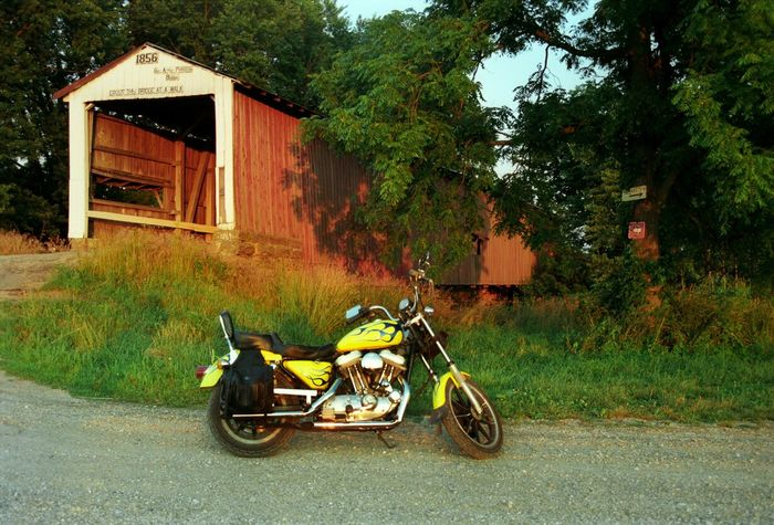 Red covered bridge and a yellow Harley Davidson Light And Shadow Bridge Bridges Covered Bridge Harleydavidson Harley Davidson Harley Motorcycles Motorcycle Eye4photography  HarleyDavidsonMotorcycles Harley-Davidson Harleydavison Harley Davidson Sportster Motorcycle Photography Taking Pictures CoveredBridge Color Bridge View Editorial  Biker Life Editorial Photography Colorful Cool Bridge Photography