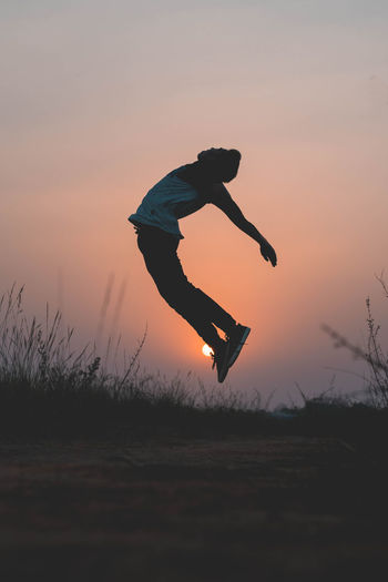 Man Jumping On Field Against Sky During Sunset