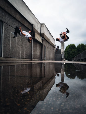 Concrete & Kinetic reflections | Shot on the Honor 10 Architecture Check This Out City City Life Exploring EyeEm EyeEm Best Shots Freerunning London Puddleography Sky And Clouds Taking Photos Architecture Explore Full Length Honor 10 Jumping Lifestyles Mid-air Puddle Real People Reflection Streetphotography Urban Water