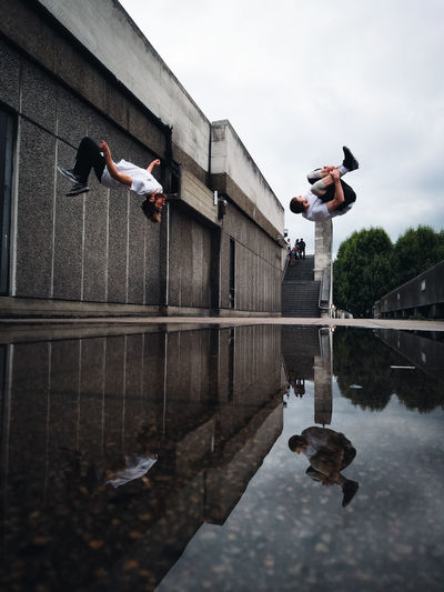 Reflection of man jumping in water