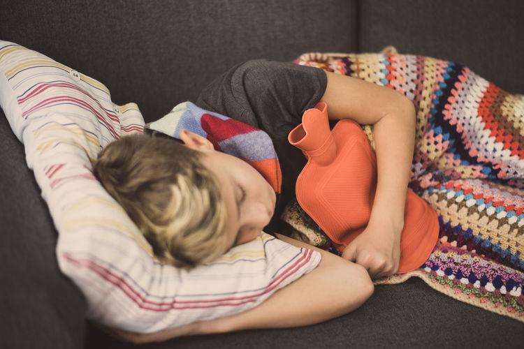Ill boy sleeping on sofa at home
