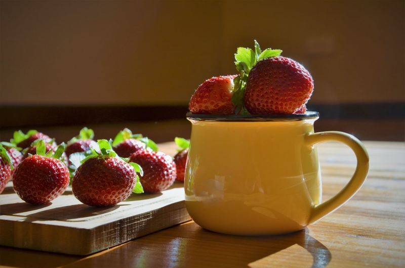 Close-up of strawberry fruits and cup on table