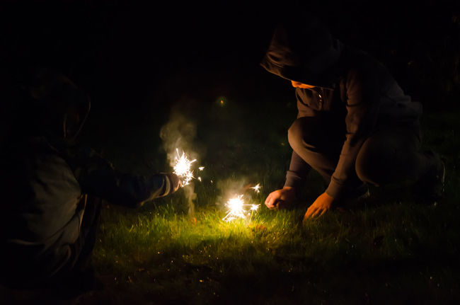 Children Dark Sparkler Boys Brothers Crouching Firework Grass Illuminated Illumination Kneeling Down Night Outdoors Outside Real People Sparklers Sparks Sparks Flying