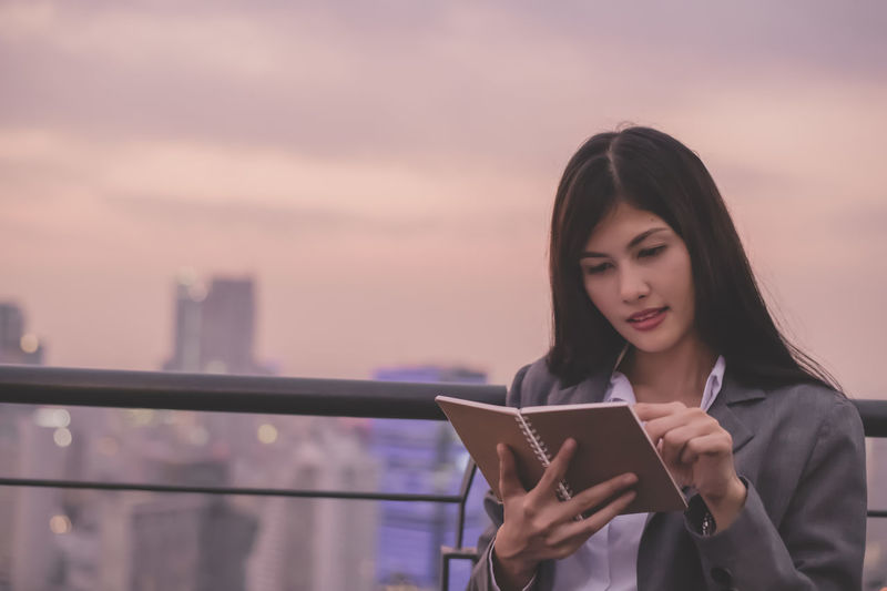 Businesswoman reading book at rooftop