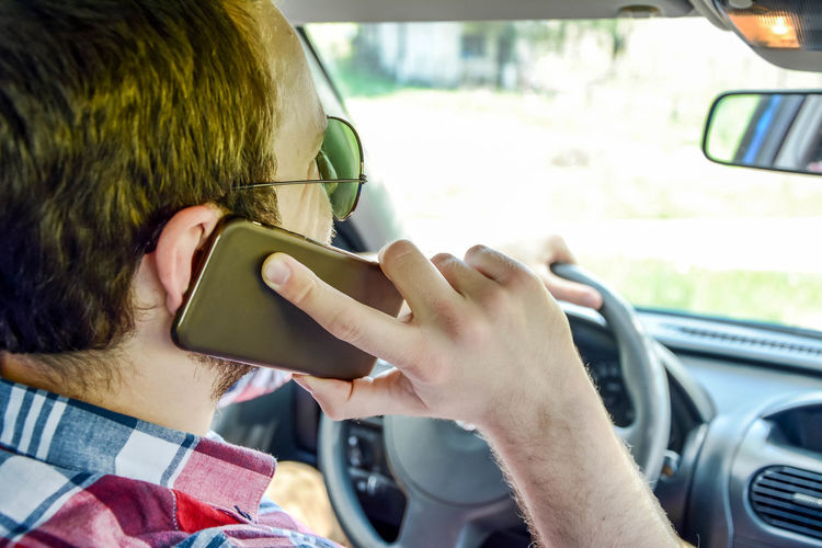 Close-up of man talking on mobile phone while driving car