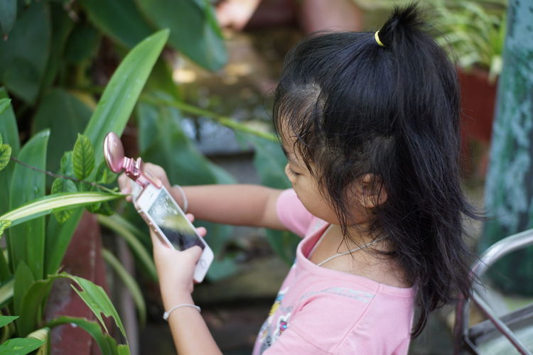 Four-year-old girl is intending to shoot with a mobile camera. Going Remote Thai Thai Girl Thailand Casual Clothing Child Childhood Day Females Focus On Foreground Girls Growth Hair Hairstyle Hand Holding Innocence Leaf Leisure Activity Lifestyles One Person Outdoors Plant Plant Part Real People Women The Portraitist - 2018 EyeEm Awards The Still Life Photographer - 2018 EyeEm Awards The Fashion Photographer - 2018 EyeEm Awards