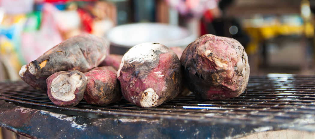 A large sweet potato is roasted on a hot charcoal stove. Hot Stove Barbecue Burn Carbohydrates Close-up Day Focus On Foreground Food Food And Drink Freshness Grill Healthy Eating Meat No People Outdoors Pink Color Root Singe Steel Grating Yam