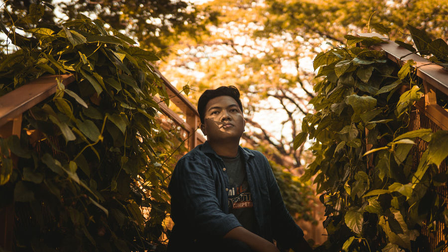 Portrait of young man standing by leaves