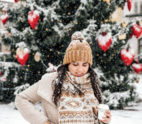 Portrait of a young woman drinking coffee from a paper coffee to go cup. winter, christmas, snowing.