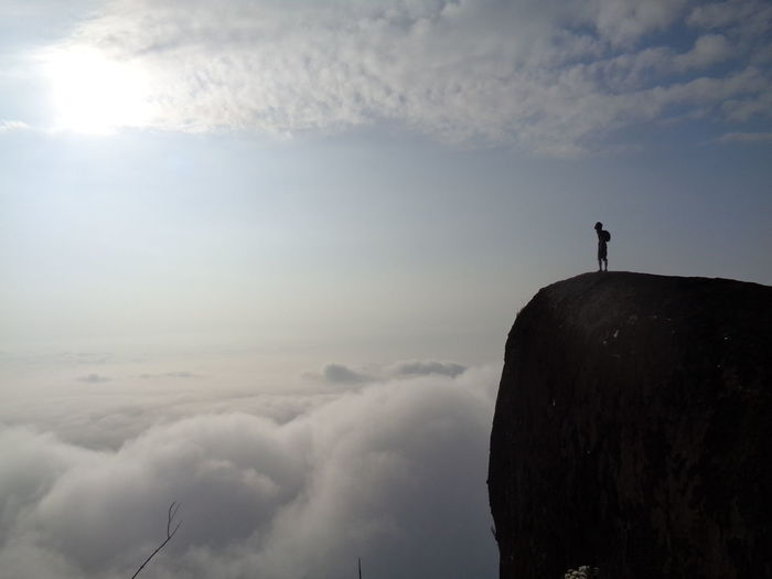 Silhouette Person Standing On Cliff By Cloudscape Against Sky