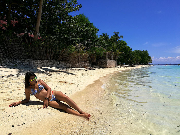Woman wearing bikini lying at beach against sky