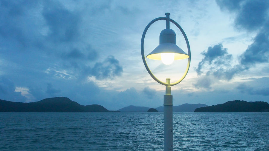 Lantern at the bay Bright Harbor Beauty In Nature Bulb Cloud - Sky Decoration Leisure Light Lighting Equipment Mountain Nature No People Outdoors Scenics - Nature Sea Sky Streetlights Tranquil Scene Tranquility Water Waterfront