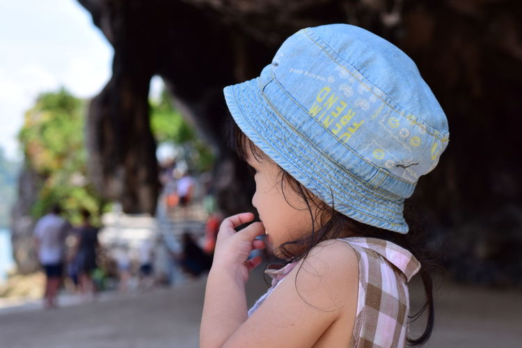 Close-Up Of Girl Wearing Hat While Eating Food Outdoors