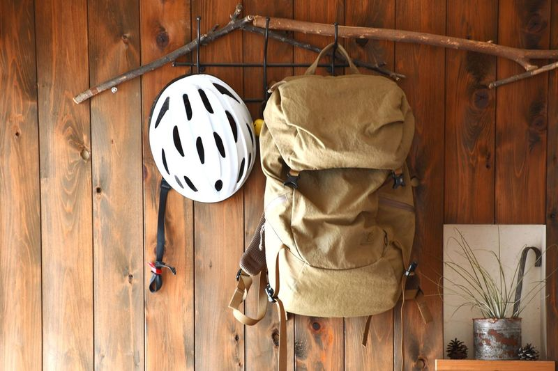Backpack and cycling helmet hanging on wooden wall