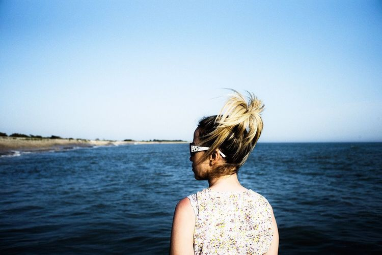Rear view of young woman standing in sea against clear sky