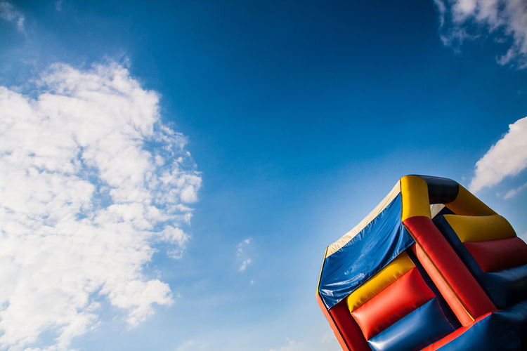 Tilt image of bouncy castle against sky