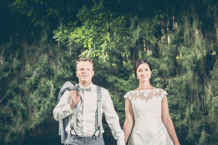 Portrait of smiling bride and groom standing against trees