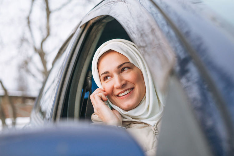 Beautiful smiling young muslim woman in headscarf using mobile in right-hand-drive car