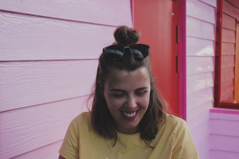 Close-Up Of Smiling Young Woman Against Wall