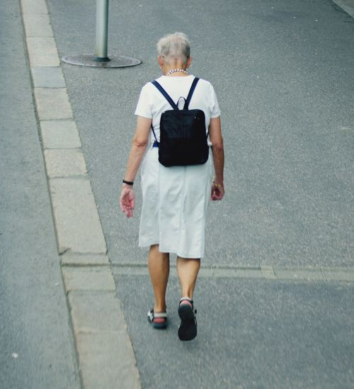 A mature lady with a rucksack on her back walking along the pavement next to the road. Dress Nature_collection EyeEm Best Shots Focus On Foreground Selective Focus Close-up High Angle View Looking Down Outdoors Motion Full Length One Person Adult Rear View Walking Senior Adult Women Senior Women Casual Clothing Footpath Lifestyles Leisure Activity Bag Day Sidewalk Real People City