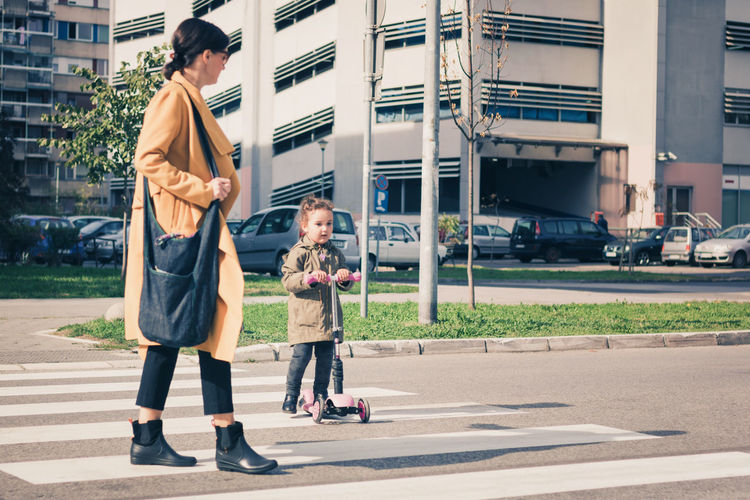 Full length of mother and daughter on street in city