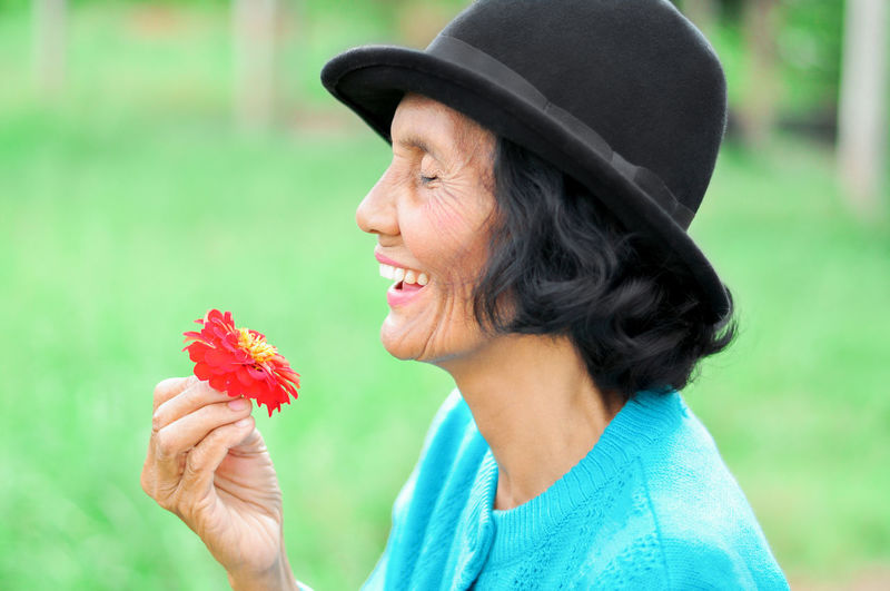 Close-up of smiling senior woman holding flower