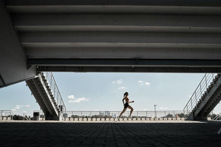 Woman walking on footpath in city against sky