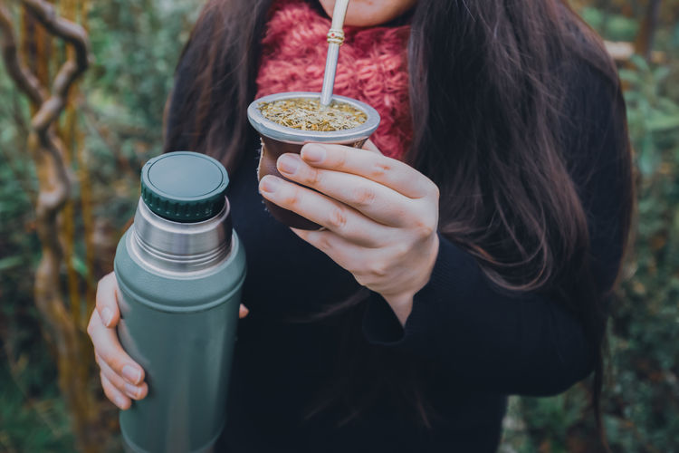 Young woman drinking mate in the park. latin beverage.
