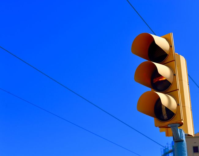 Low Angle View Of Traffic Signal Against Clear Blue Sky