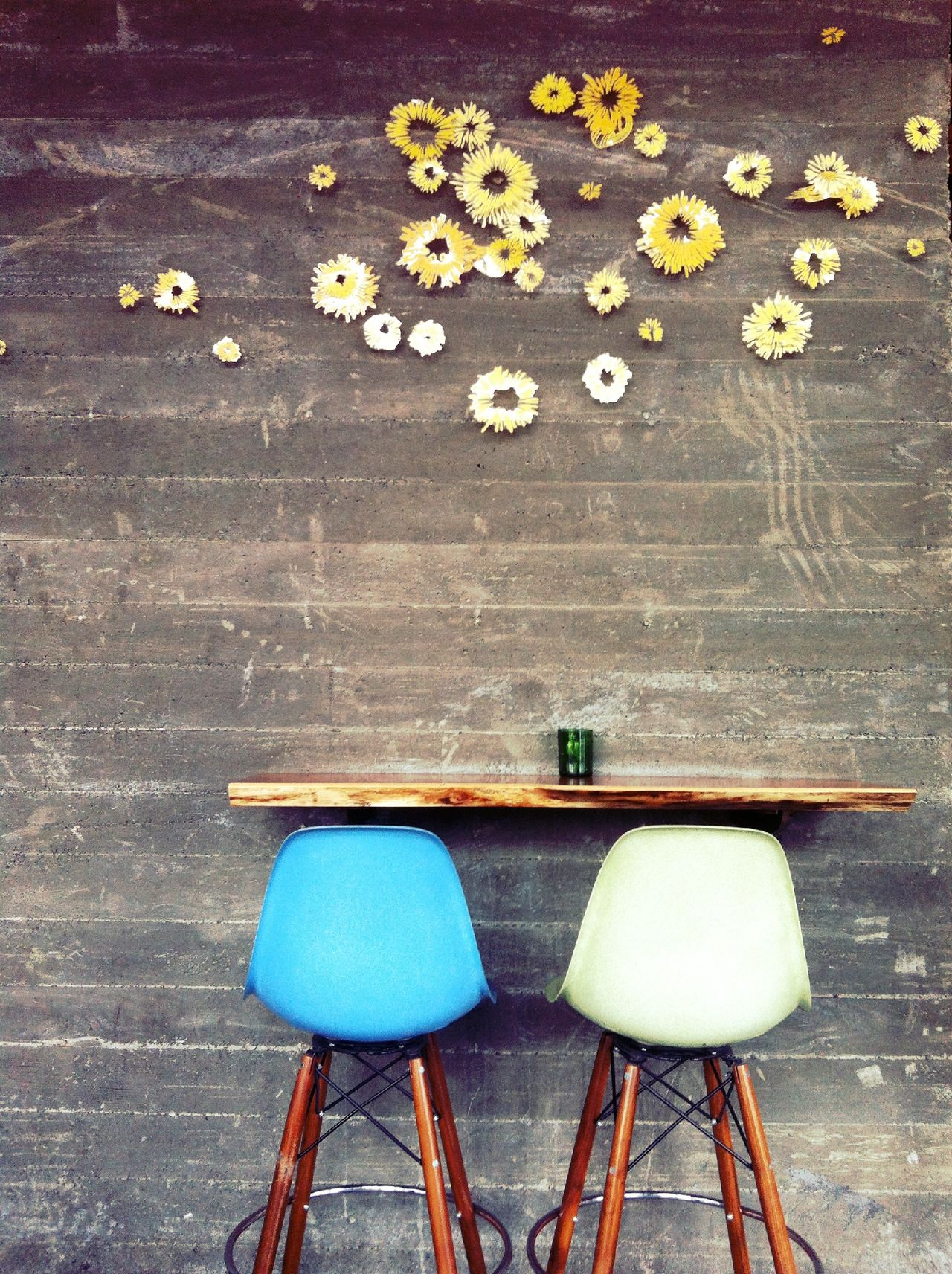 Bar stools against wooden wall