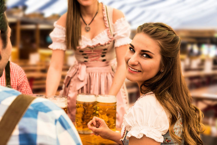Portrait Smiling Young Woman With Friends Having Beer At Table