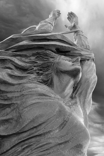 Close-up of angel statue against sky