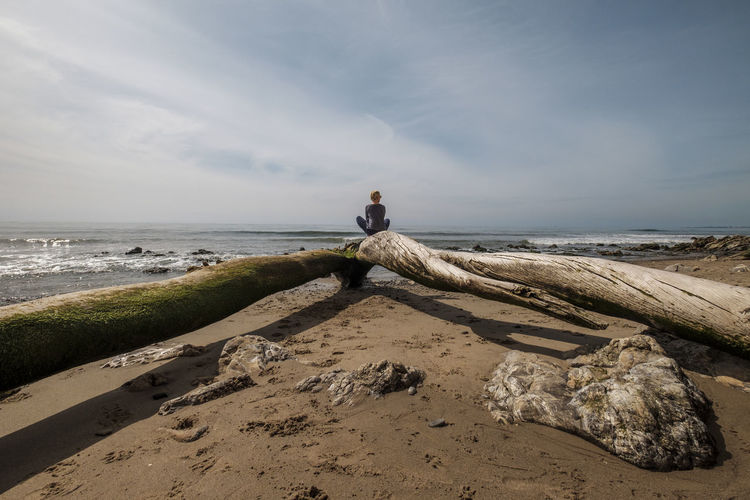Woman Sitting On Driftwood At Beach Against Sky