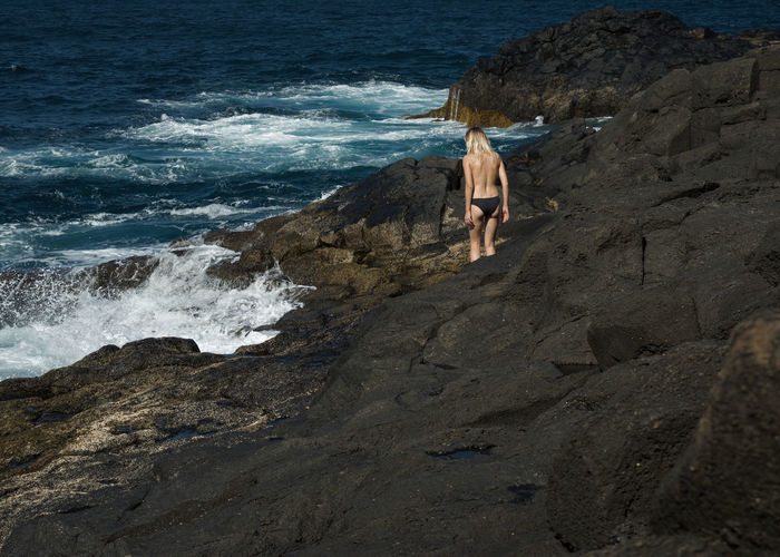 Rear view of shirtless woman walking on rocks by sea