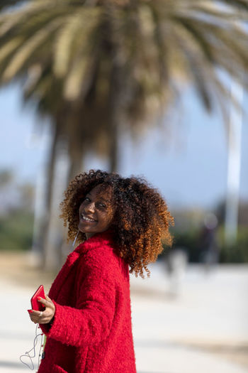 Front view of a young smiling curly afro woman standing outdoors while smiling and looking away in a sunny day One Person Curly Hair Red Hairstyle Women Standing Hair Portrait Focus On Foreground Lifestyles Adult Young Adult Day Leisure Activity Waist Up Looking At Camera Tree Casual Clothing Young Women Beautiful Woman Outdoors Frizzy Woman African American Afro Denim Happiness Happy Fun Daylight Sunlight