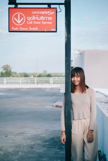 Portrait of woman standing by road sign