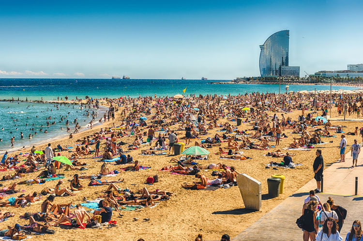 BARCELONA - AUGUST 10: People enjoying a sunny day on La Barceloneta beach, Barcelona, Catalonia, Spain, on August 10, 2017 Sea Water Land Crowd Sky Large Group Of People Group Of People Beach Architecture Real People Nature Day Lifestyles Sand Built Structure Building Exterior Sunlight Leisure Activity Travel Destinations Horizon Over Water Outdoors