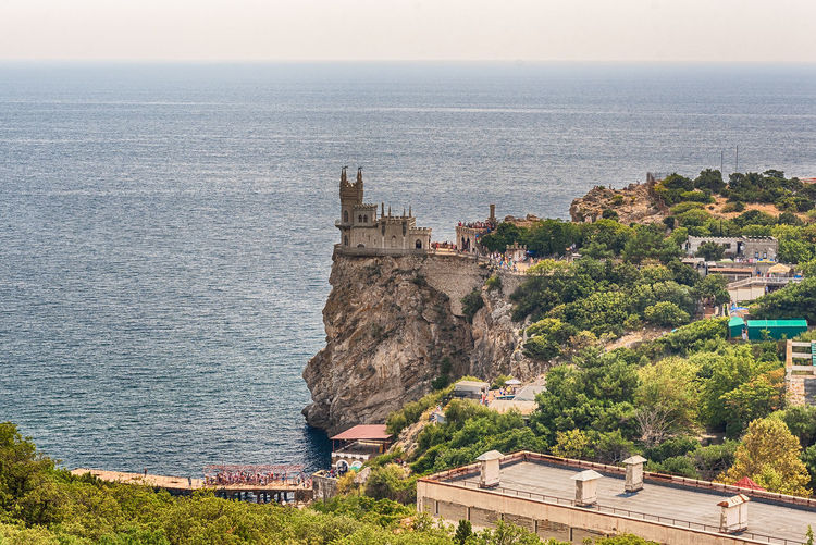 Swallow's nest, scenic castle and iconic landmark over the Black Sea in Yalta, Crimea Architecture Beauty In Nature Building Building Exterior Built Structure Day High Angle View Horizon Horizon Over Water Land Nature No People Outdoors Plant Scenics - Nature Sea Sky Travel Destinations Tree Water