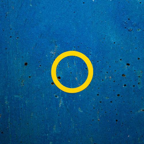 Close-up of yellow circle on blue wall