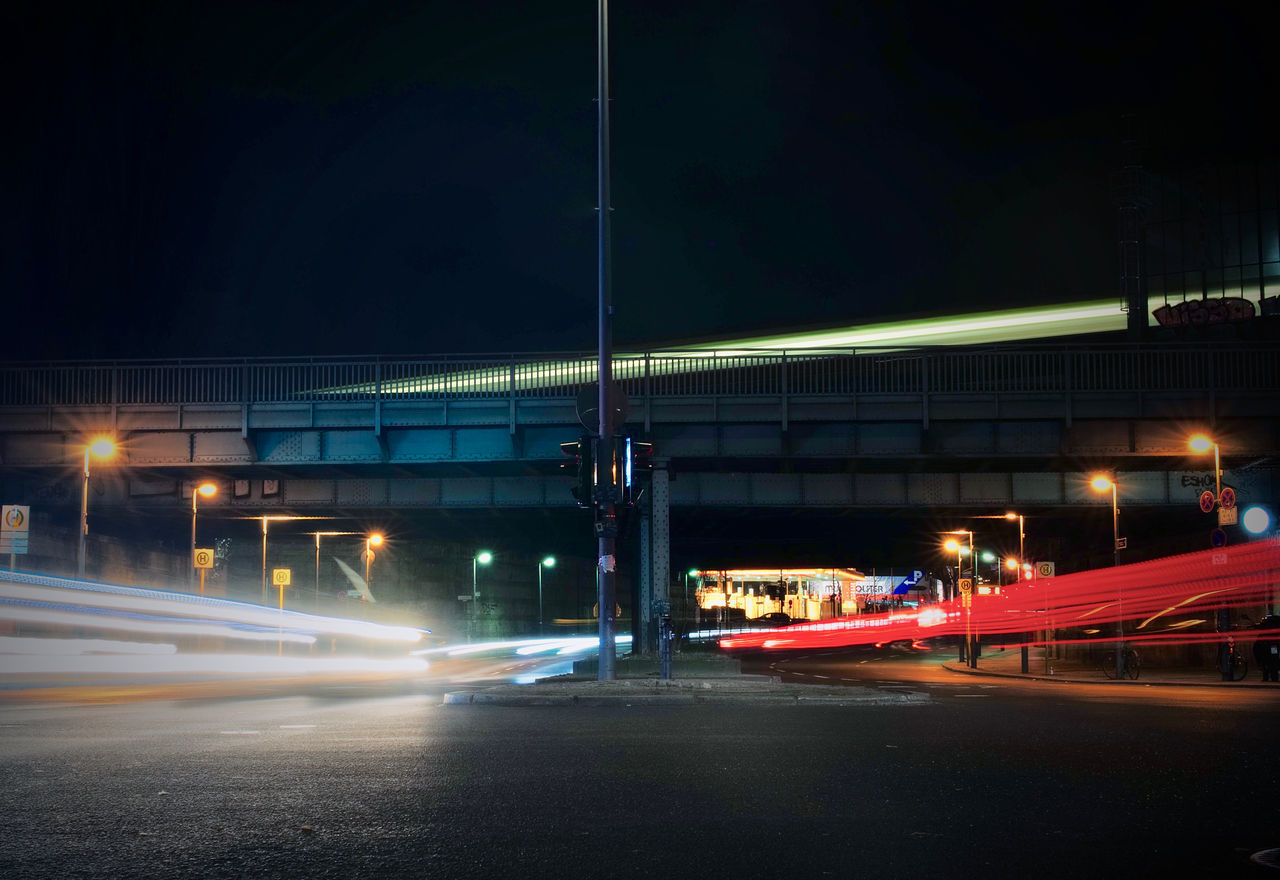 TRAFFIC LIGHT TRAILS ON ROAD IN CITY AT NIGHT