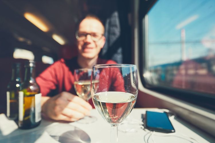 Portrait Of Mid Adult Man With Wineglass On Table Sitting In Train