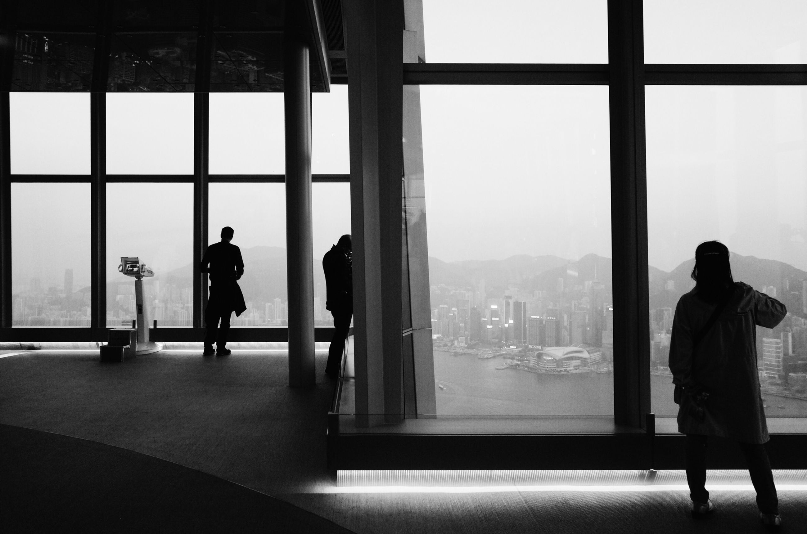 indoors, window, glass - material, lifestyles, men, transparent, rear view, standing, person, silhouette, full length, leisure activity, architecture, looking through window, built structure, day, sitting